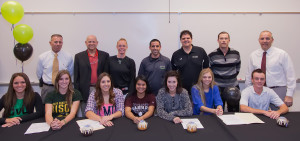 Coaches Keairnes, Atwell, Glass, Clarke, Siqueiros, Steffenhagen and Principal Phillips stand behind seniors Haley Harrison, Breanna Beatty, Rachel Williams,  Melissa Lacro, Brooke Stover, Stephanie Herman and Brandon Bauman as they sign their letters of intent for college sports careers.