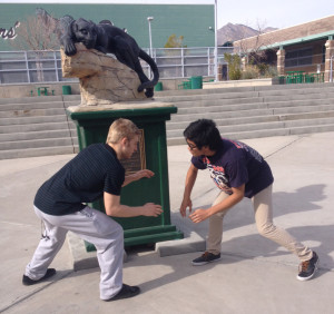 Wrestling captains Kayden Pierson and Michael Tim strike a fierce wrestling pose in front of the prowling panther that guards the quad.