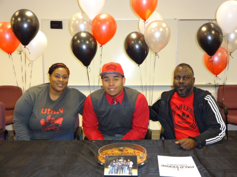Senior Michael Hughes and his parents smile proudly after he signed a letter of intent for UNLV on Feb. 5 in the Principal's Conference Room.