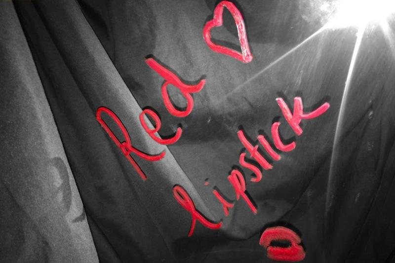 """The sharp red words """"Red Lipstick"""" as written on a mirror pops from an otherwise black and white background."""