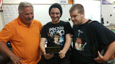 Mr. Dervan, adviser for Sci-Fi Video Game Club, and seniors Dillon Powell, president of the club, and Jake Rainey look at the games on their Nintendo 3DS.